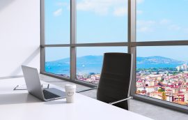 A workplace with laptop and a cap of coffee in a modern panoramic office, New York City view, Manhattan. A concept of financial consulting services. 3D rendering.
